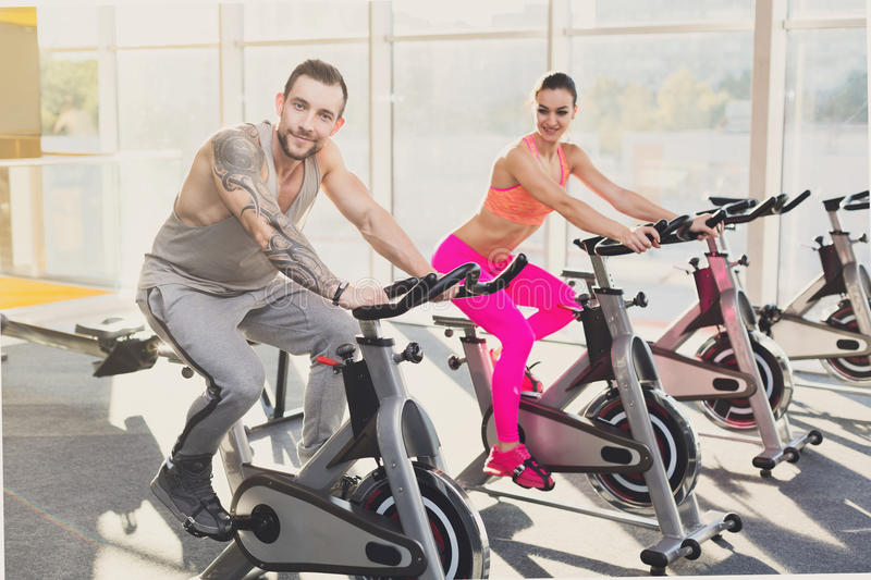 Man and woman, couple in gym on exercise bikes stock images