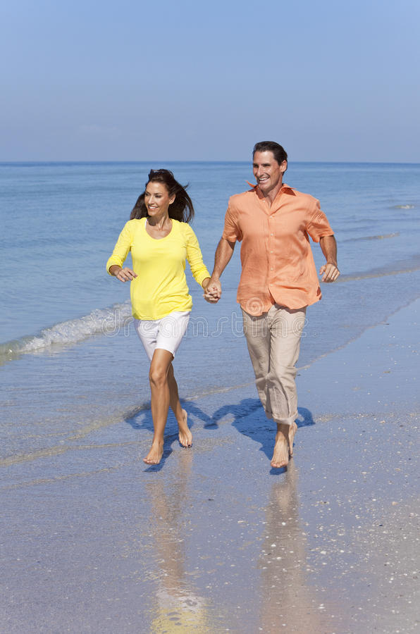 Download Man & Woman Couple Running On An Empty Beach Royalty Free Stock Photography - Image: 23095257