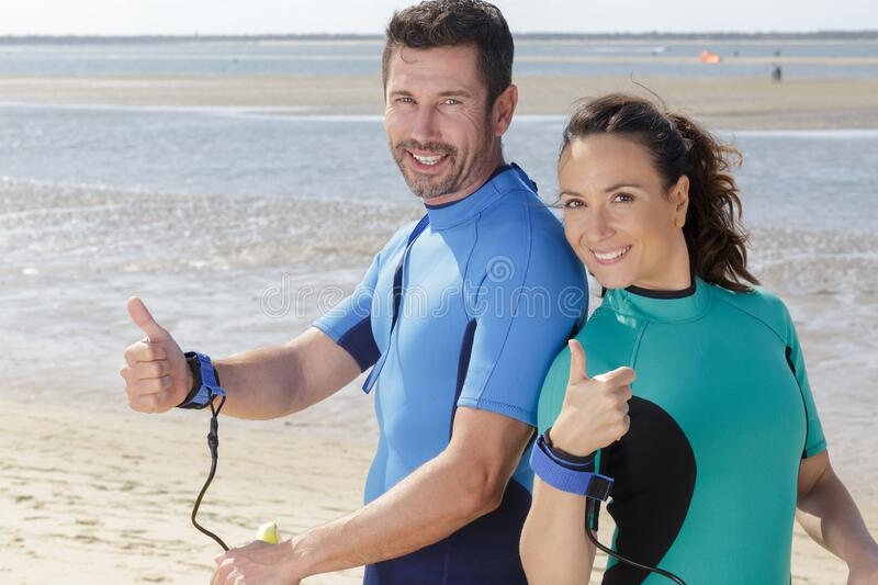 Man woman couple surfboards surfing on beach stock photos