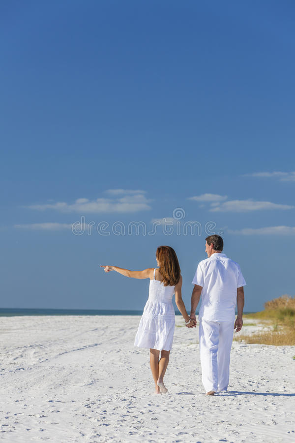 Man Woman Couple Walking Pointing on Empty Beach royalty free stock images