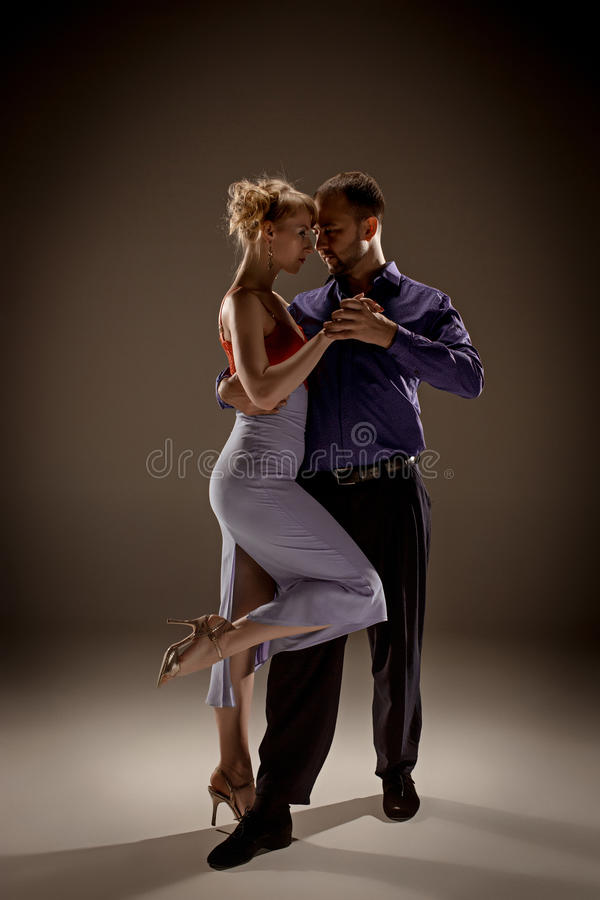 The man and the woman dancing argentinian tango. A men and a women dancing argentinian tango on gray studio background royalty free stock photography