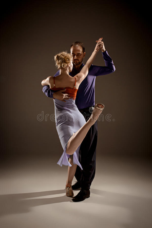 The man and the woman dancing argentinian tango. A men and a women dancing argentinian tango on gray studio background royalty free stock photos
