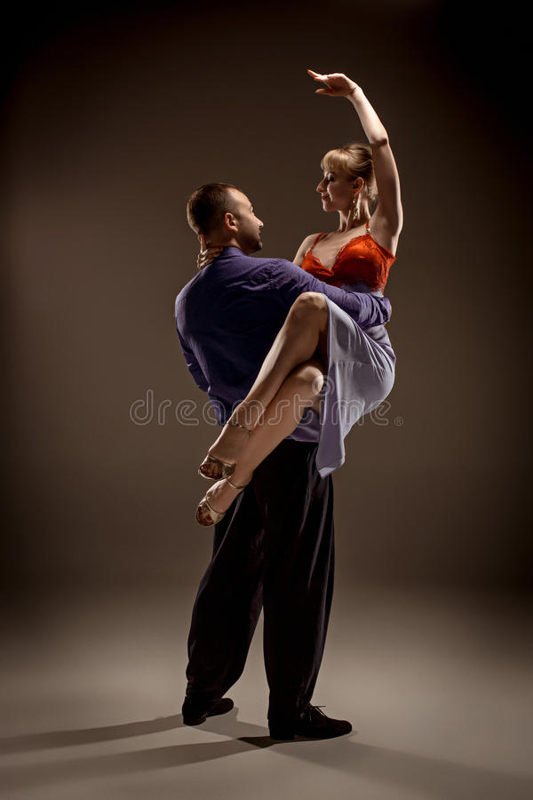 The man and the woman dancing argentinian tango. A men and a women dancing argentinian tango on gray studio background royalty free stock images