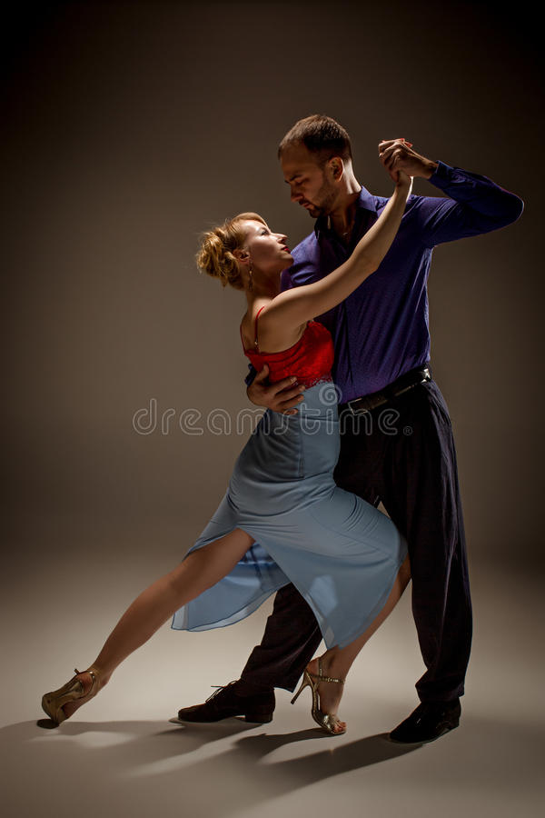 The man and the woman dancing argentinian tango. A men and a women dancing argentinian tango on gray studio background stock image