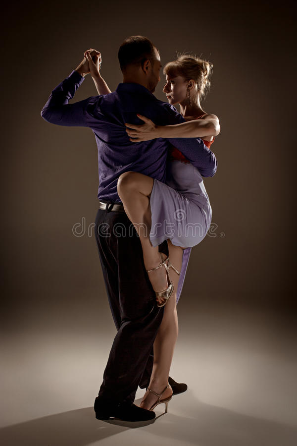 The man and the woman dancing argentinian tango. A men and a women dancing argentinian tango on gray studio background royalty free stock photo