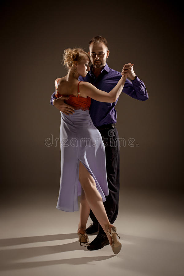 The man and the woman dancing argentinian tango. A men and a women dancing argentinian tango on gray studio background stock photo