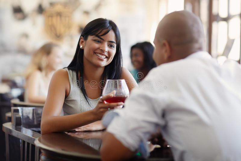 Man and woman dating at restaurant. Young adult hispanic couple dining out in restaurant and toasting with cocktails. Horizontal shape, front view, focus on stock images