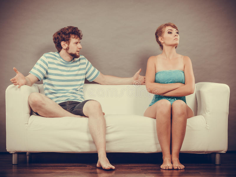 Man and woman in disagreement sitting on sofa. Bad relationship concept. Man and women in disagreement. Young couple sitting on couch at home having quarrel royalty free stock photos