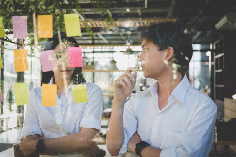 Man & woman discussing creative idea with adhesive notes on glass wall at workplace. Sticky note paper reminder schedule. Asian men & women discussing creative stock photos