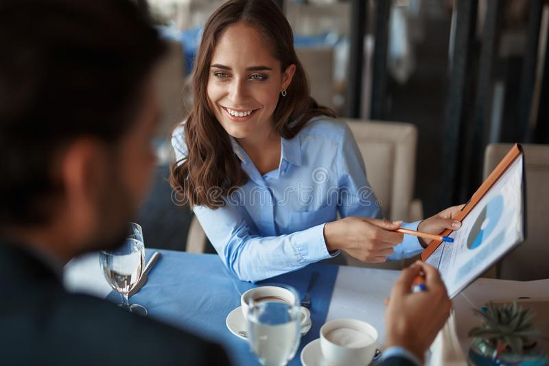 Man and woman discussing work project in restaurant. Business lunch in friendly atmosphere. Close up portrait of young smiling businesswoman explaining work stock photography