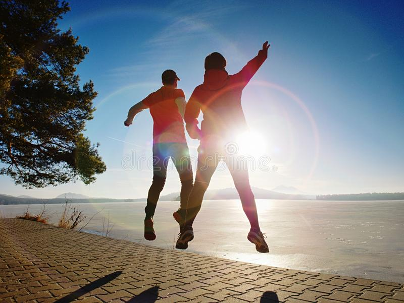 Man and woman do sports at lake against strong morning Sun stock image