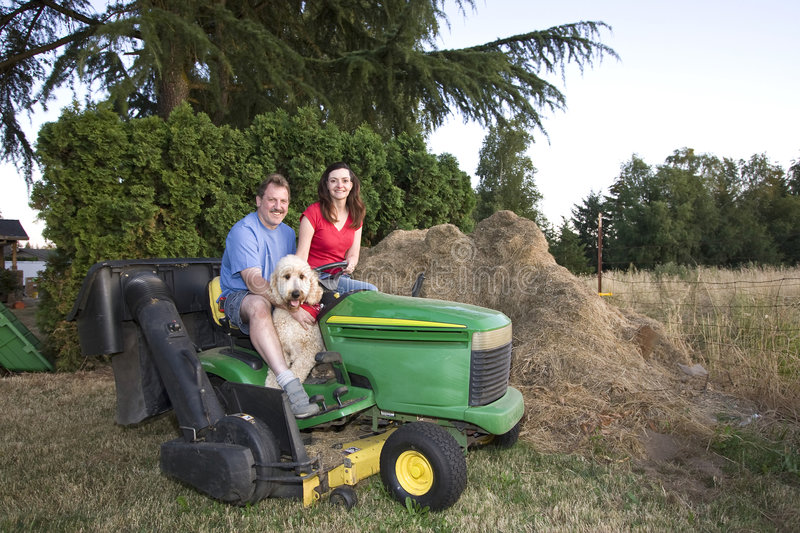 Man, Woman, and Dog on a Tractor - Horizontal royalty free stock photo