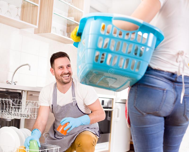 Man and woman doing chores together. Young couple doing chores together. Man loading dishwasher and wife holding laundry basket royalty free stock photo