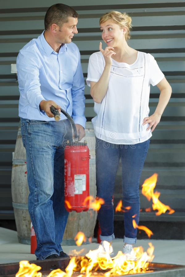 Man and woman doing fire extinguishing drill. Man and women doing a fire extinguishing drill stock photo