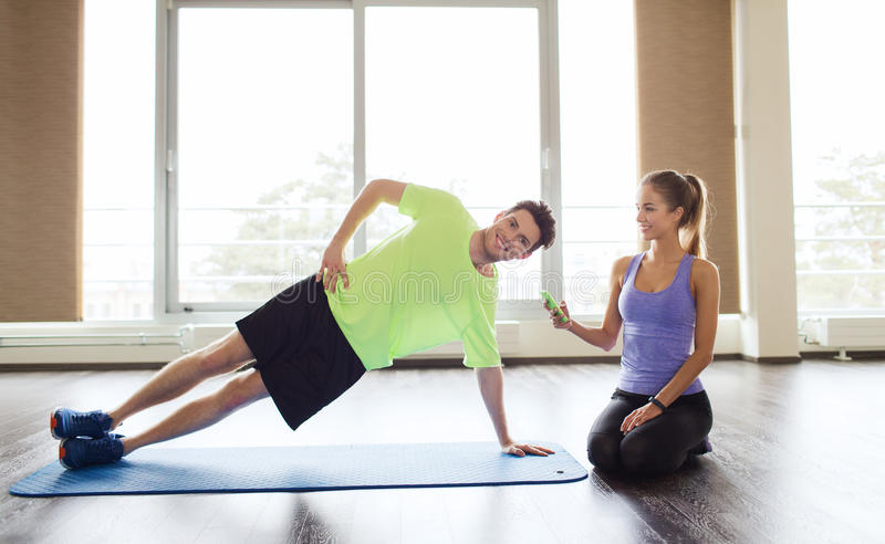 Man and woman doing plank exercise on mat in gym. Fitness, sport, technology and people concept - men and women with smartphone doing side plank exercise on mat stock image