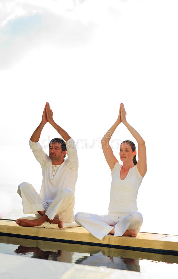 Man and woman doing yoga near the sea royalty free stock image