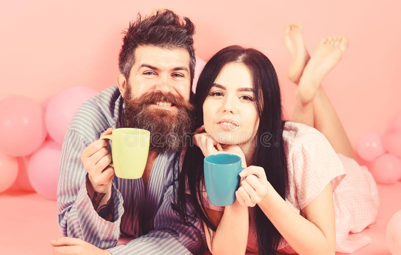 Man and woman in domestic clothes, pajamas. Man and woman on smiling faces lay, pink background. Couple in love drink royalty free stock images