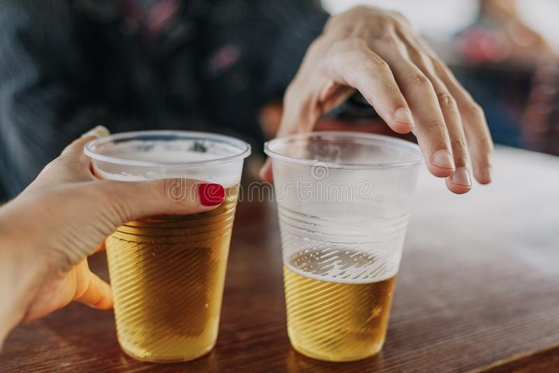 Man and woman are drinking beer. Gender difference. A hand with a woman with a manicure holds a full glass of beer. The second glass in the man hand is partially stock image