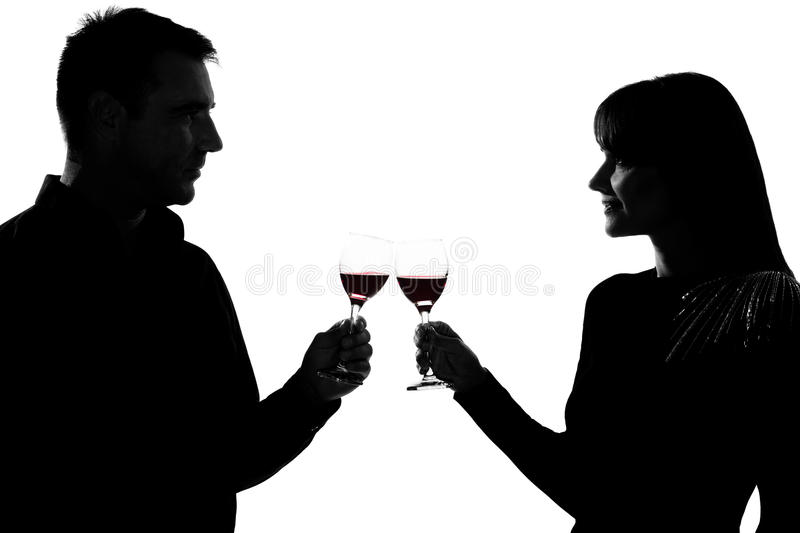 Man and woman drinking red wine toasting. One caucasian couple men and women drinking red wine toasting in studio silhouette isolated on white background stock image