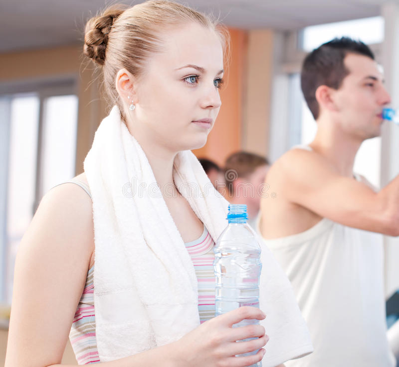 Man and woman drinking water after sports in gym royalty free stock photography