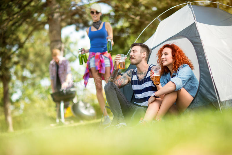 Man and woman drinks beer in front of tent at camping. Young men and women drinks beer in front of tent at summer camping in nature royalty free stock photography