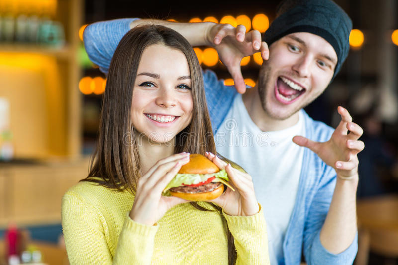 Man and woman eating burger. Young girl and young man are holding burgers on hands. Burger concept stock photography