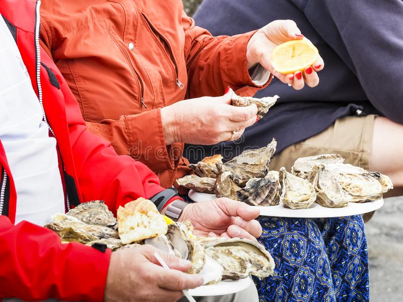 Man and woman eating oysters on white plate lunch time outdoor royalty free stock photo
