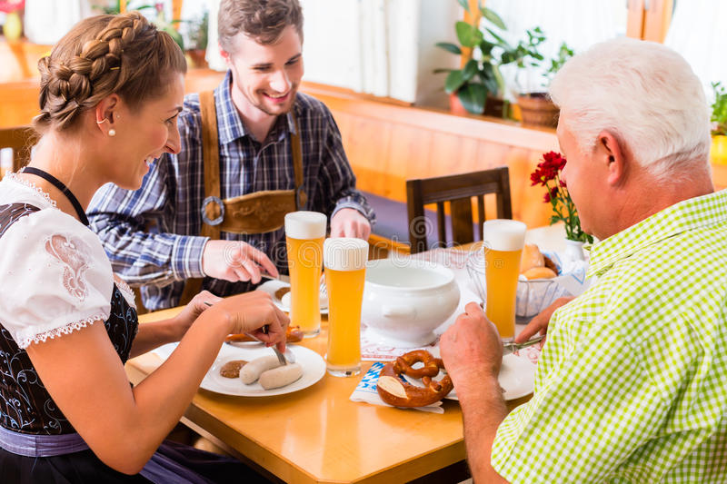 Man and woman eating in restaurant. Man and women eating in bavarian restaurant stock images