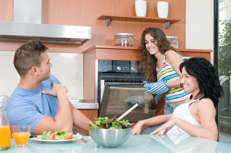 Man and woman eating salada and woman at the oven royalty free stock images