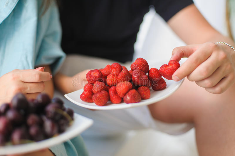 Man, woman eating strawberries and cherries stock photos