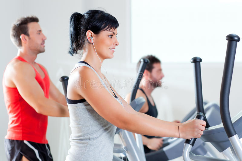 Man and woman with elliptical cross trainer at gym royalty free stock images