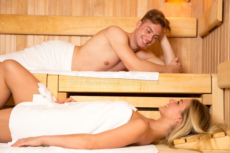Man and a woman enjoying wellness day in sauna royalty free stock image