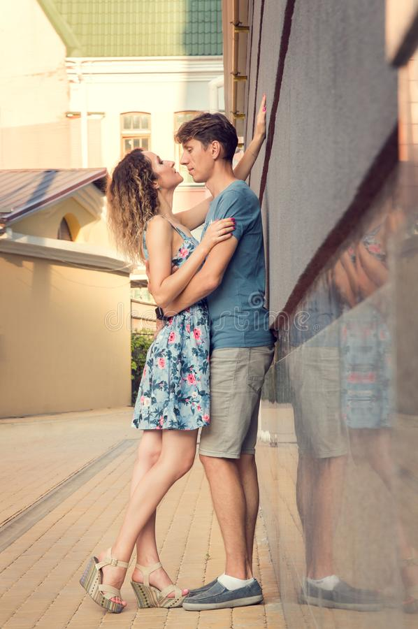 A man and a woman are entwined in a loving embrace. Sunlit courtyard in the background. Romance. A men and a women are entwined in a loving embrace. Sunlit royalty free stock photo