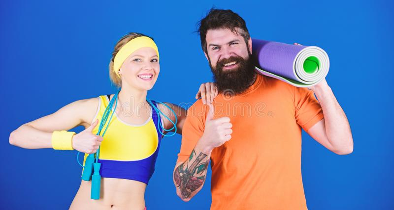 Man and woman exercising with yoga mat and jump rope. Fitness exercises. Workout and fitness. Girl and guy live healthy. Man and women exercising with yoga mat stock images