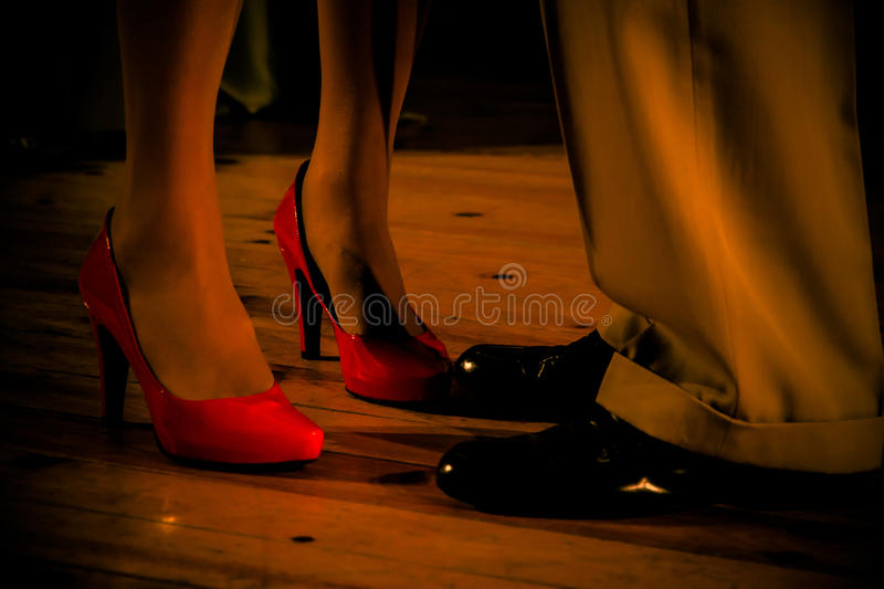 Man and Woman Feet Head to Head. Feet and legs of man and woman ( facing each other ) inside . She heeled red shoes and black shoes . Suggested conversation or stock image