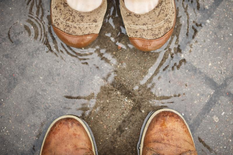 Man and woman feet in a puddle, top view. Male and female shoes opposite each other. Couple love and relationships concept royalty free stock photo