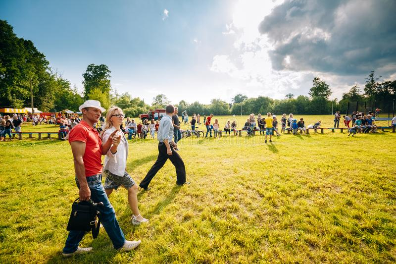 Man and woman at the festival of youth. Dobrush, Belarus. Dobrush, Belarus - June 25, 2017: A man and a woman are walking along the field on which they celebrate royalty free stock images