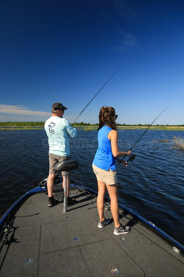 Man and Woman Large Mouth Bass Fishing in Boat. A man and woman fish for large mouth bass in the Creole Nature Reserve in Southwest Louisiana royalty free stock photos