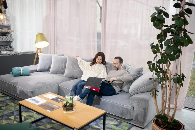 Man and woman in furniture salon looking interested stock photography