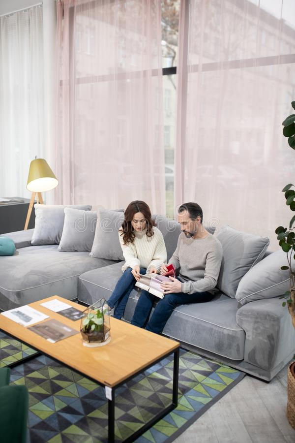 Man and woman in furniture salon looking involved stock photos