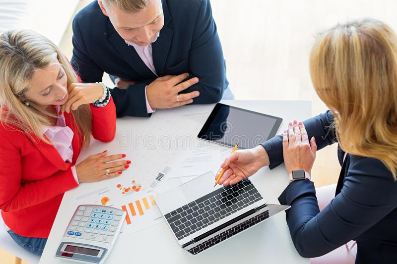 Man and woman getting help from professional financial consultant stock images