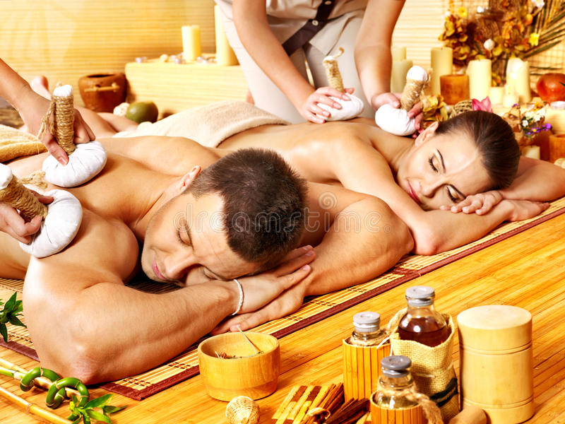 Man and woman getting herbal ball massage in spa. stock photo