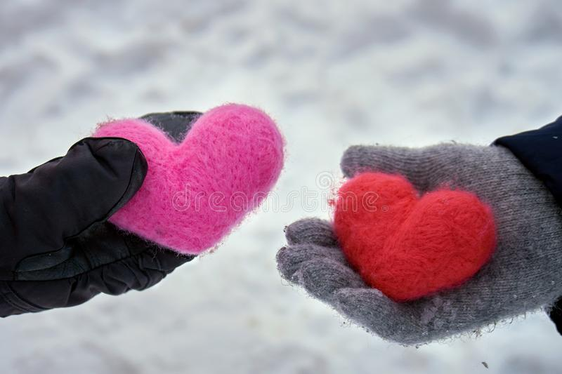 Man and a woman giving woolen hearts to each other outdoors in winter stock images