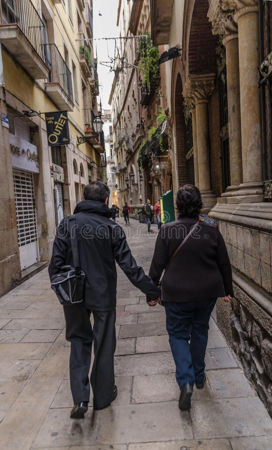 Editorial usage. Barcelona, Spain, Gothic Quarter, November 2018, man and woman go hand in hand along a narrow street. Man and woman go hand in hand along a royalty free stock image