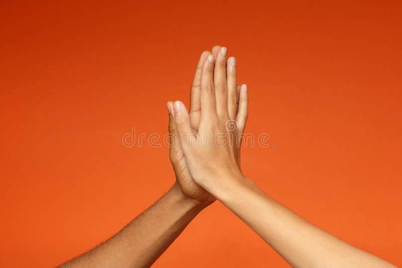 Man and woman greeting each other with high five stock image