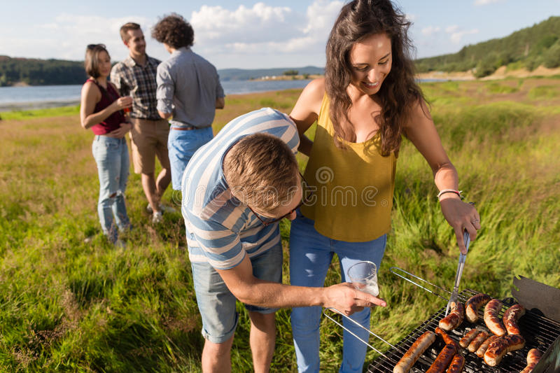 Man and woman grilling bratwurst on barbecue grill. Young men and women grilling sausages on barbecue grill at party in nature stock image