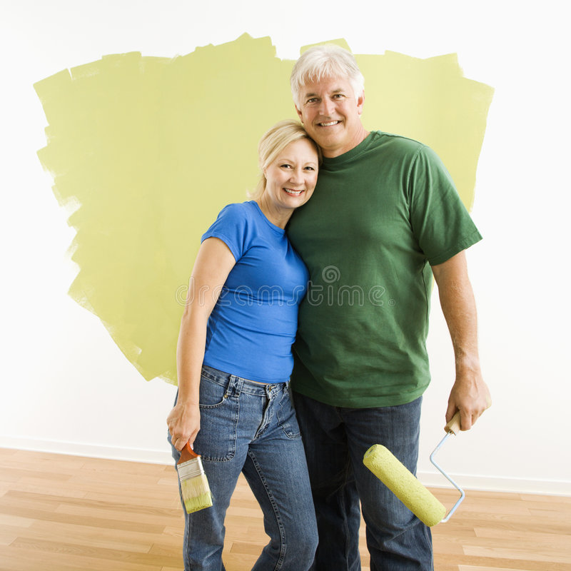 Man and woman with half-painted wall. royalty free stock photography
