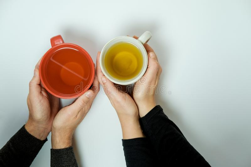 Man and woman hands with cups of tea on white background royalty free stock images