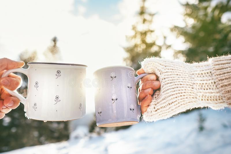 Man and woman hands in knitting mittens taking cups of hot drink stock image