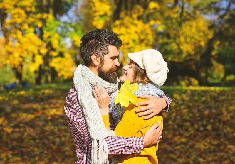 Man and woman with happy faces on autumn trees background. stock photo